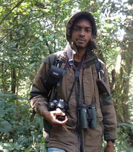 aghah valery binda in raincoat in forest with binoculars